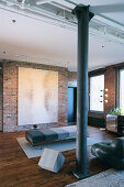 Lounger in different shades of grey in front of artwork in loft apartment with brick walls