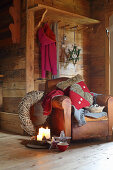 Vintage leather armchair and Christmas decorations in rustic wooden cabin
