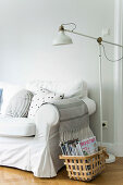 Basket of magazines and standard lamp next to sofa