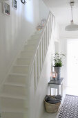Console table and runner next to staircase in white hallway
