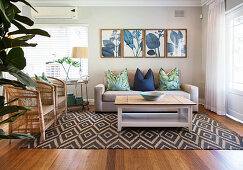 Wicker armchairs, couch and coffee table on geometric rug below botanical print on wall of living room