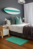 Surfboard on grey wall above bed