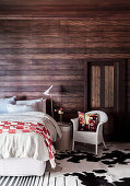 Double bed, bedside table and rattan armchair in the bedroom with dark wood paneling