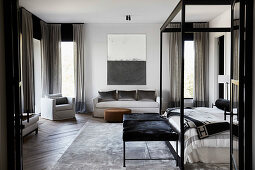 Spacious bedroom with four-poster bed, clothes bench, silver-colored carpet and sofa set
