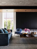 Blue upholstered sofa, fur-look chair and coffee table in open living room