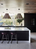 Elegant kitchen island with marble worktop, bar stool and hanging lamps in an open living room
