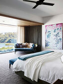 Double bed, painting and blue sofa in spacious bedroom with glass front