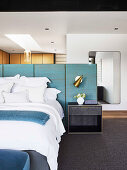 Double bed and bedside table on blue panel as bed headboard and room divider in the bedroom