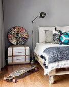 Pallet bed on castors, vintage accessories and skateboard in teenager's bedroom