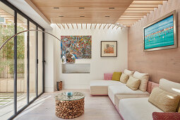 Small, bright living room with glass wall leading onto terrace