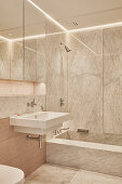 Small, marble-clad bathroom with large mirrored cabinet