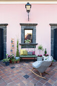 Rocking chair, foliage plants, bench and mirrored window with lava stone frame on pink wall of courtyard