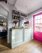 Decorative signs with various mottoes above sideboard next to hot-pink lattice door