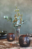 Tealight holders flanking vase of eucalyptus leaves and waxflowers