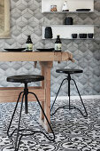 Rustic wooden table and black stools in kitchen with black-and-white patterned floor tiles