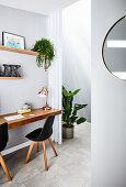 Schwebender Schreibtisch mit schwarzen Stühlen, neben Durchgang mit Zimmerpflanze