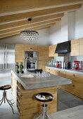 Modern kitchen with wooden cabinets and concrete worksurface in chalet