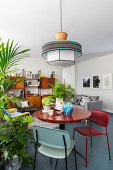 Round table, houseplants and chairs in open-plan interior
