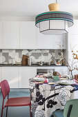 Bistro table set with colourful tablecloth and chairs in front of white kitchen counter