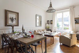 Rustic dining table and pale sofa set in room with white walls