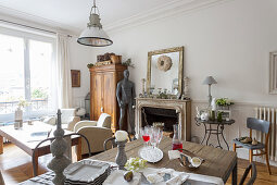 View across rustic dining table to fireplace, sculpture, wooden cupboard and seating area