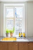 Küchenzeile mit Holzfronten unter dem Altbaufenster