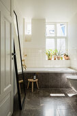 Bathroom with dark stone tiles in period building