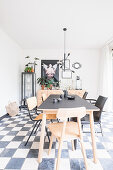 Different chairs around dining table on chequered floor