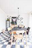 Verschiedene Stühle um den Esstisch auf Schachbrettboden