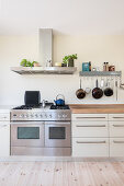 Modern gas cooker below extractor hood and hook rail in bright kitchen