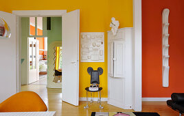Brightly coloured walls and retro furnishings in living room