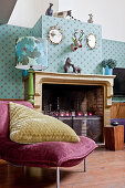Velvet easy chair with large cushion in front of old fireplace and patterned wallpaper