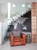 Brauner Ledersessel neben Treppengeländer aus Glas