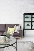 Graues Sofa, Couchtisch mit Glasplatte und Vitrinenschrank im Wohnzimmer