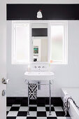 Pedestal sink under interior window in black and white bathroom