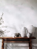 Rustic wooden console with vases and containers next to olive trees