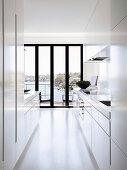 Weiße Designerküche mit Balkontür und Meerblick