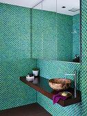 Spiegelschrank und Waschtisch im Bad mit Mosaikfliesen in Grüntönen