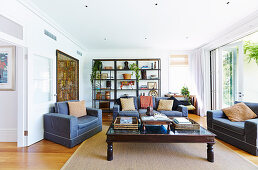 Blaue Polstergarnitur und antiker Couchtisch im Wohnzimmer, im Hintergrund offenes Regal mit Kunstwerken