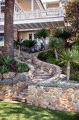 Weg mit Natursteinen führt durch Palmengarten zum Haus