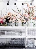 Roses in glass vases, glass jars on the shelf