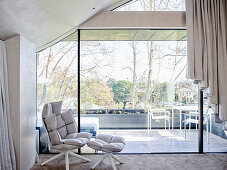 Designer armchair with ottoman in front of glass front