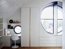 Table and chair next to elegant built-in wardrobe, view through porthole into the open