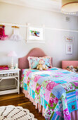 Bed with colorful patchwork blanket in girl's room