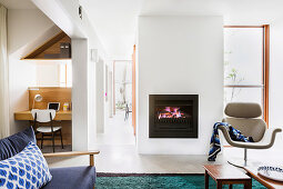 Armchairs in front of a fireplace and integrated home office in an open living room