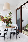 Round table with branches of leaves and white chairs in front of open sliding patio door