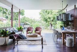 Essbereich mit langem Tisch und Lounge auf überdachter Terrasse