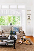 Upholstered sofa in beige, coffee table and dog on sisal carpet in the living room