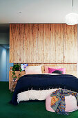 Double bed in front of room divider with wooden paneling