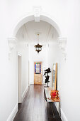 White hallway with round arch and dark plank floor